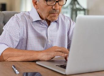 uomo anziano controlla portatile usato